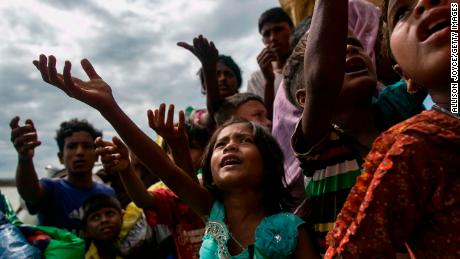 SHAH PORIR DIP, BANGLADESH - SEPTEMBER 14: Rohingya beg for food after arriving on a boat to Bangladesh on September 14, 2017 in Shah Porir Dip, Bangladesh. Around 370,000 Rohingya refugees have fled into Bangladesh since late August during the outbreak of violence in the Rakhine state. Myanmar's de facto leader Aung San Suu Kyi announced that she will miss next week's UN General Assembly as criticism on her handling of the Rohingya crisis grows while her government has been accused of ethnic cleansing. According to reports, the total death toll from Rohingya boat capsize incidents rose to 84 while many people have died trying to get out, including children and infants. (Photo by Allison Joyce/Getty Images)
