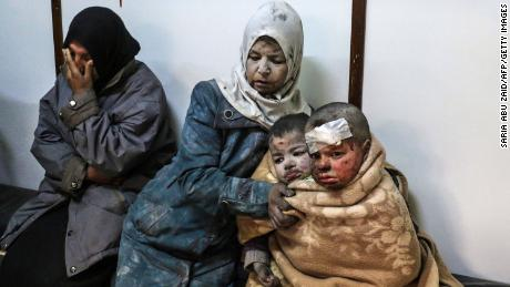 Injured children and women wait at a hospital following a reported strike by Syrian government forces near Damascus, on February 20.