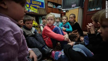 First-grade students, including 6-year-old Sasha, center, participate in a school drill to respond to shelling in eastern Ukraine.