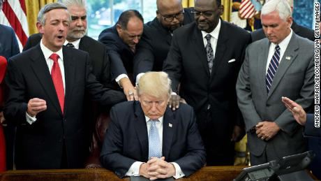 US President Trump bows his head during a prayer led by faith leaders and evangelical ministers after signing a proclamation declaring a day of prayer for victims of Hurricane Harvey in September.