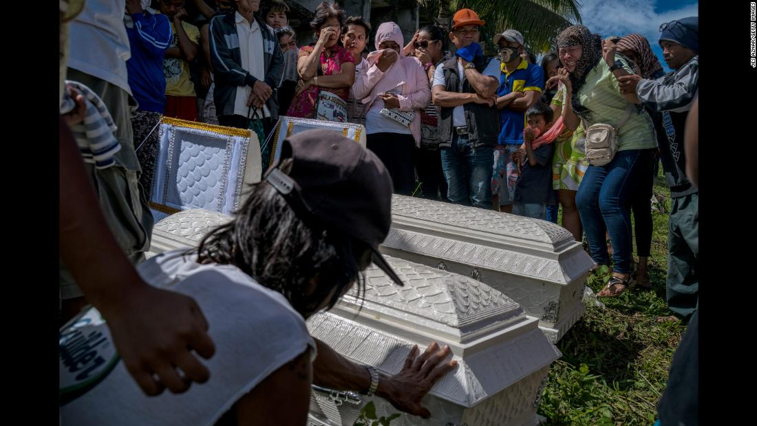 Family and friends mourn those who perished during Tropical Storm Tembin in Tubod, Philippines, on December 26.