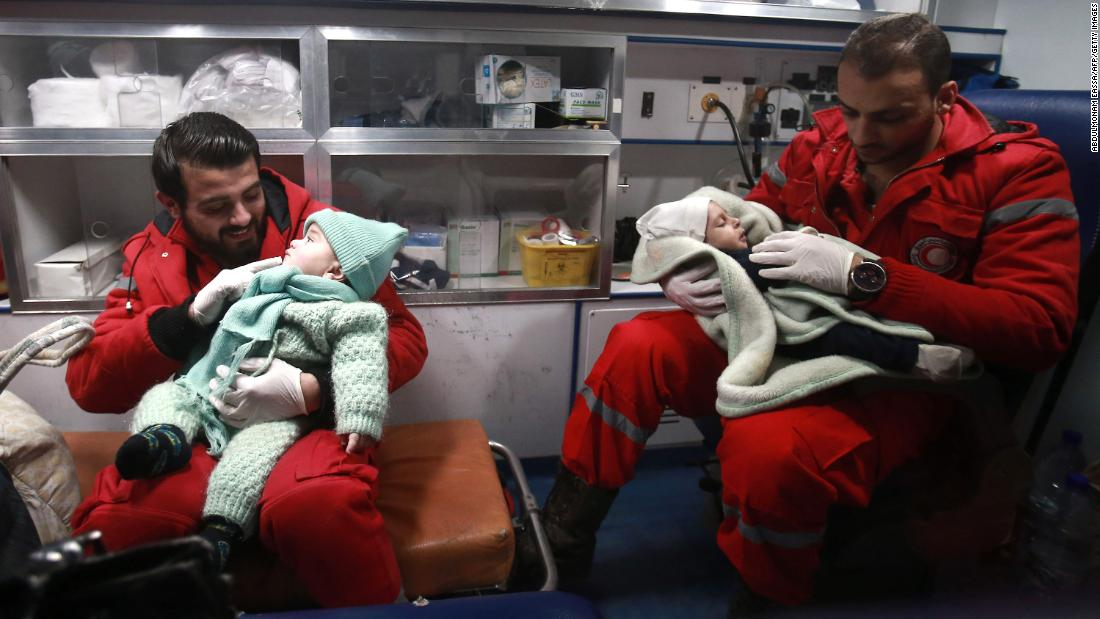 Paramedics distract children inside an ambulance on December 27, the second night of an evacuation operation led by the Syrian Red Crescent and the International Committee of the Red Cross in Douma, Syria, on the outskirts of the capital of Damascus.