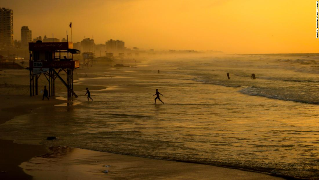 "People walk on the beach of Gaza City at sunset on Sunday, December 24. <a href=""http://www.cnn.com/2017/12/21/world/gallery/week-in-photos-1222/index.html"" target=""_blank"">See last week in 34 photos.</a>"