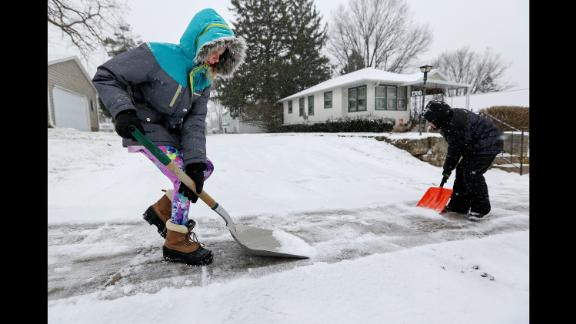 Karlee Winter and her brother Samuel Espinoza shovel snow from their neighbor