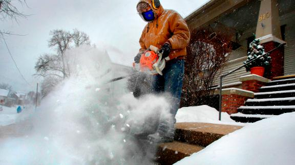 Jose Nieto uses a leaf blower to clear snow from the steps of a sick neighbor