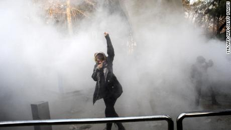 An Iranian woman raises her fist as she makes her way through a cloud of tear gas.