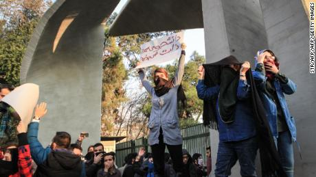 Students hold placards in protest at the University of Tehran.