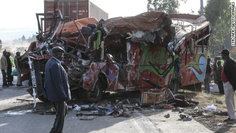 People look at the wreckage of a bus and a lorry that crashed in a head-on collision, killing thirty people, at the accident scene near Nakuru, Kenya, on December 31, 2017. Thirty people were killed and 16 injured early on the morning of December 31 in a head-on collision between a bus and a lorry on a road in central Kenya, police said. The accident occurred close to a notorious stretch on the Nakuru-Eldoret highway when a bus travelling from Busia, in western Kenya, collided with a truck coming from Nakuru. Police said the death toll for that stretch of road has now reached 100 this month alone. / AFP PHOTO / STR        (Photo credit should read STR/AFP/Getty Images)