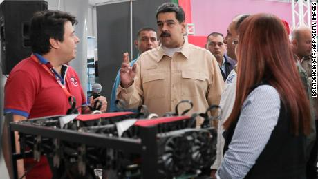 Venezuelan President Nicolas Maduro(C) speaks in front of a computer used to mine crypto currency Ethereum at the International Science and Technology Fair (FITEC) in Caracas on December 3, 2017. Venezuela is creating a digital currency to combat a financial blockade by the United States, President Nicolas Maduro announced Sunday. The Petro will be backed by Venezuela's oil and gas reserves and its gold and diamond holdings according to Maduro. / AFP PHOTO / PRESIDENCIA        (Photo credit should read PRESIDENCIA/AFP/Getty Images)