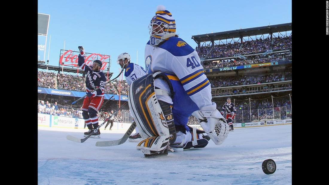 New York Rangers forward Paul Carey, left, celebrates after scoring on Buffalo goalie Robin Lehner on Monday, January 1. The Rangers triumphed 3-2 in the NHL Winter Classic, which was played at Citi Field, home of the New York Mets baseball team.