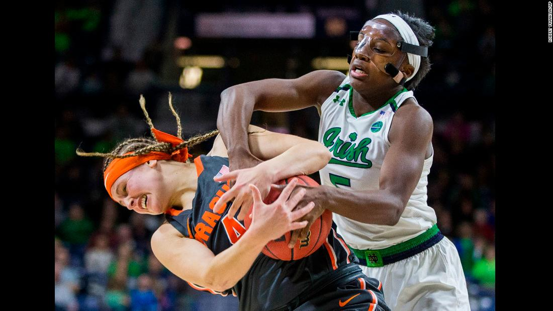Syracuse's Tiana Mangakahia, left, wrestles for the ball with Notre Dame's Jackie Young during a college basketball game in South Bend, Indiana, on Thursday, December 28.