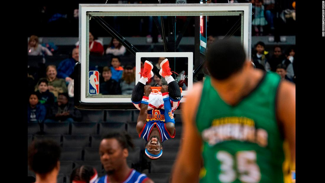 "Jahmani ""Hot Shot"" Swanson, one of the Harlem Globetrotters, hangs on the rim after a dunk in New York on Tuesday, December 26."