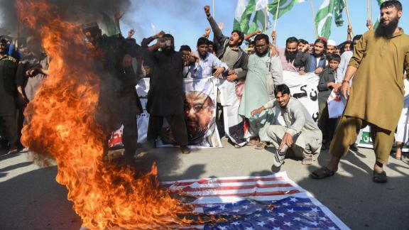 Activists burn the American flag at a protest in Karachi on Tuesday.