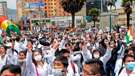Medicine students and doctors march in downtown La Paz, during protests against a new law that penalizes medical malpractice, on December 22, 2017.   Doctors in Bolivia completed a month long strike on Friday, amid requests from the government, the Catholic Church and even the United Nations to resume services and dialogue over a new law which penalizes medical malpractice. / AFP PHOTO / Jorge Bernal        (Photo credit should read JORGE BERNAL/AFP/Getty Images)