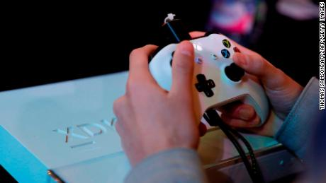 A gamer plays video games with a Xbox console during the 2017 Paris Games Week exhibition at the Porte de Versailles exhibition centre in Paris. / AFP PHOTO / Thomas SAMSON        (Photo credit should read THOMAS SAMSON/AFP/Getty Images)