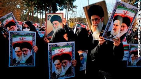 TOPSHOT - Pro-government demonstrators hold posters of Iran's supreme leader, Ayatollah Ali Khamenei (L) and Iran's founder of Islamic Republic, Ayatollah Ruhollah Khomeini during a march in Iran's holy city of Qom, 130 kilometres south of Tehran on January 3, 2018, as tens of thousands gathered across Iran in a massive show of strength for the Islamic rulers after days of deadly unrest. / AFP PHOTO / Mohammad ALI MARIZAD        (Photo credit should read MOHAMMAD ALI MARIZAD/AFP/Getty Images)