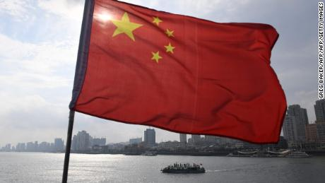 A Chinese tour boat cruises on the Yalu River behind the Chinese flag flying on the Broken Bridge, in the border city of Dandong, in China's northeast Liaoning province on September 5, 2017. The Broken Bridge once connected Dandong and the North Korean town of Sinuiju, but was bombed by the US during the Korean war and now only reaches half way across the Yalu River. / AFP PHOTO / GREG BAKERGREG BAKER/AFP/Getty Images