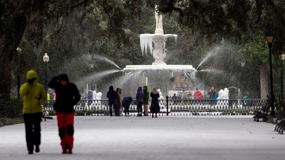 Visitors walk around the frozen fountain and snow covered sidewalks at Forsyth Park, Wednesday, Jan. 3, 2018, in Savannah, Georgia.