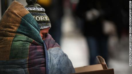 A homeless man tries to stay warm on a Manhattan street on an unseasonably cold day on March 15, 2017 in New York City.