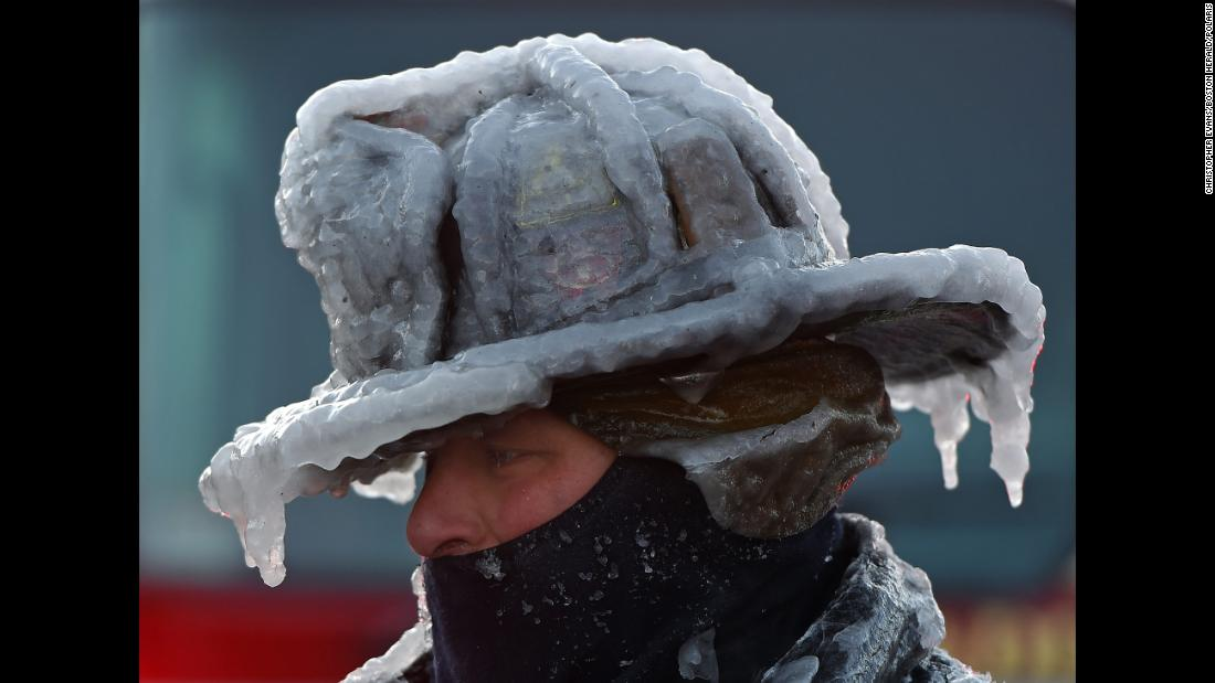 Firefighter Bobby Lehman, with his helmet and gear caked in ice, tries to thaw out after battling a fire in Nahant, Masschusetts, on Monday, January 1.