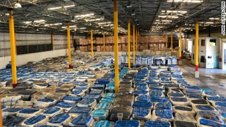 In December, 20,000 tarp rolls sit idle in a government warehouse.