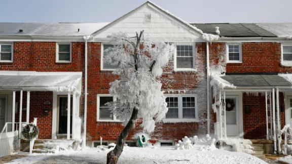 A tree and rowhouse are partially covered by ice after a water main break in Catonsville, Maryland, on January 3.