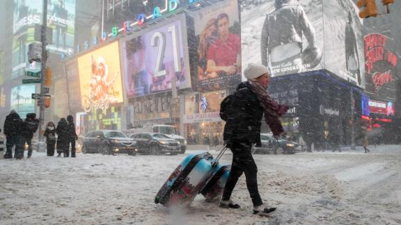 Rebecca Hollis drags her suitcases through New York's Times Square on January 4.