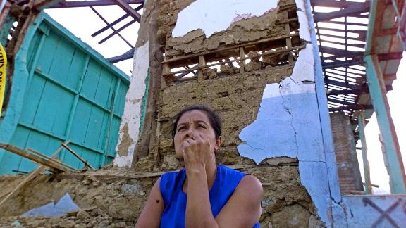 A woman sits before her earthquake-destroyed house January 29, 2001 in Armenia, El Salvador,  40kms (26 miles) west of San Salvador.