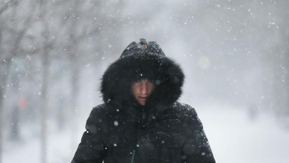 """A man walks through the streets of Boston as snow begins on January 4. The brutal cold comes after a """"bomb cyclone"""" dumped more than a foot of snow across eight states."""