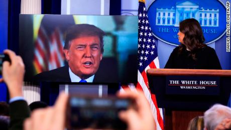President Donald Trump speaks via a video monitor to journalists in the Brady press briefing at the White House in Washington during a press briefing with press secretary Sarah Huckabee Sanders, Thursday, Jan. 4, 2018.