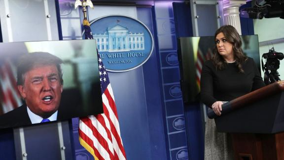 """WASHINGTON, DC - JANUARY 04:  U.S. President Donald Trump speaks via a video as White House Press Secretary Sarah Sanders listens during a daily news briefing at the James Brady Press Briefing Room of the White House January 4, 2018 in Washington, DC. Sanders spoke on various topics including the new book """"Fire and Fury"""",  written by Michael Wolff.  (Photo by Alex Wong/Getty Images)"""