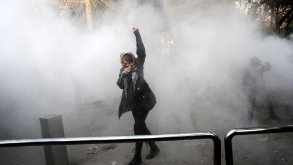 TOPSHOT - An Iranian woman raises her fist amid the smoke of tear gas at the University of Tehran during a protest driven by anger over economic problems, in the capital Tehran on December 30, 2017. Students protested in a third day of demonstrations sparked by anger over Iran
