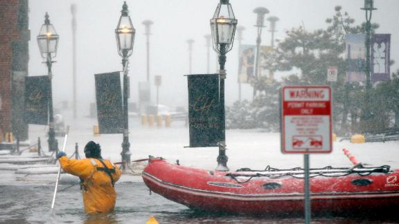 A firefighter wades through floodwaters from Boston Harbor this week on Long Wharf in Boston.