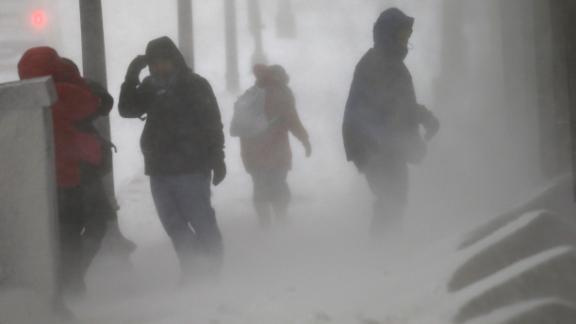 Pedestrians struggle in high winds and snow in downtown Boston on January 04.