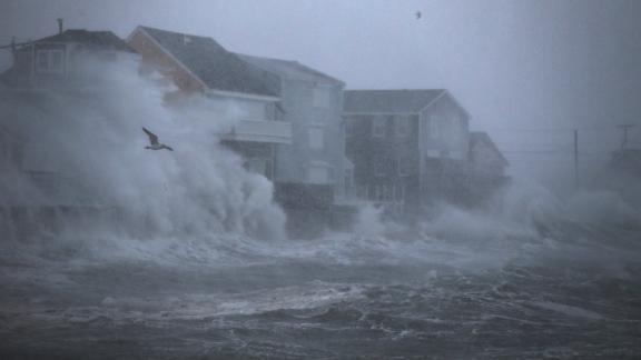 Waves crash against homes Thursday in Scituate, Massachusetts.