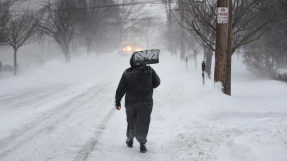 A man carries a shovel up the middle of a street in Greenwich, Connecticut, on January 4.