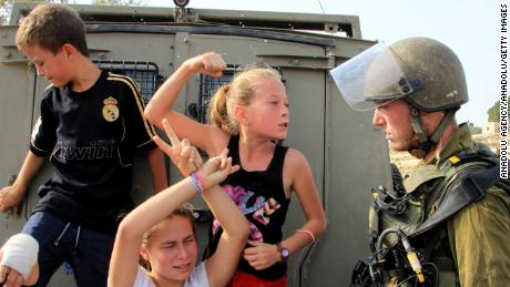 Ahed Tamimi (C) raises her fist to an Israeli soldier during a protest in Ramallah in 2012.