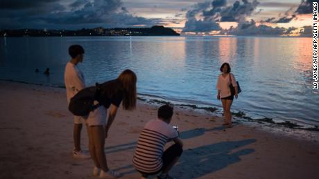 This photograph taken on August 12, 2017, shows a South Korean family on a beach at Tumon Bay in Guam. / AFP PHOTO / Ed JONES        (Photo credit should read ED JONES/AFP/Getty Images)