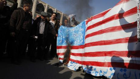 Iranian pro-government demonstrators set a makeshift US flag on fire during a march after the weekly Muslim Friday prayers in Tehran on January 5, 2018.