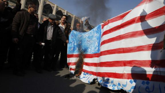 Iranian pro-government demonstrators set fire to a makeshift US flag during a march after Friday prayers in Tehran.