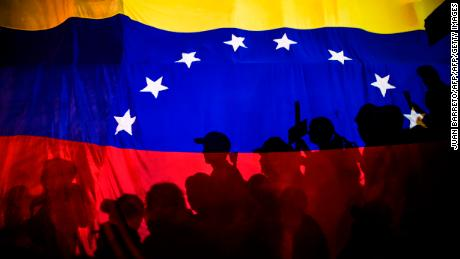 TOPSHOT - Opposition activists, seen here behind a Venezuelan flag, protest against the deaths of 43 people in clashes with the police during weeks of demonstrations against the government of Venezuelan President Nicolas Maduro, in Caracas on May 17, 2017.  The United States warned on Wednesday at the United Nations that Venezuela's crisis was worsening and could escalate into a major conflict similar to Syria or South Sudan. / AFP PHOTO / JUAN BARRETO        (Photo credit should read JUAN BARRETO/AFP/Getty Images)