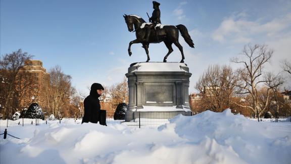 A pedestrian walks by a statue of George Washington in Boston
