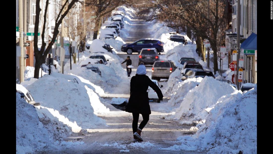 Mollie Lane carries a shovelful of snow down a street while digging her car out in Boston on January 5.