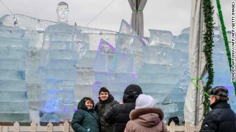 Visitors take pictures with an ice sculpture of Ronaldo in the background