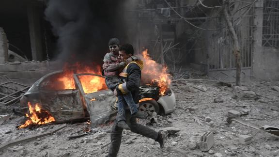 A Syrian paramedic carries an injured child following airstrikes in Eastern Ghouta on January 6.