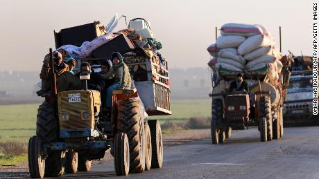 "Displaced Syrians who fled the fighting in Idlib province's southeastern town of Sinjar drive on a road in a rebel-held area near the city of Saraqib on January 7, 2018. Syrian troops captured Sinjar, the ""biggest town in southeast Idlib"", from Syria's former Al-Qaeda affiliate and were within 14 kilometres (9 miles) of the Abu al-Duhur military base, the British-based Syrian Observatory for Human Rights said.  / AFP PHOTO / OMAR HAJ KADOUR        (Photo credit should read OMAR HAJ KADOUR/AFP/Getty Images)"