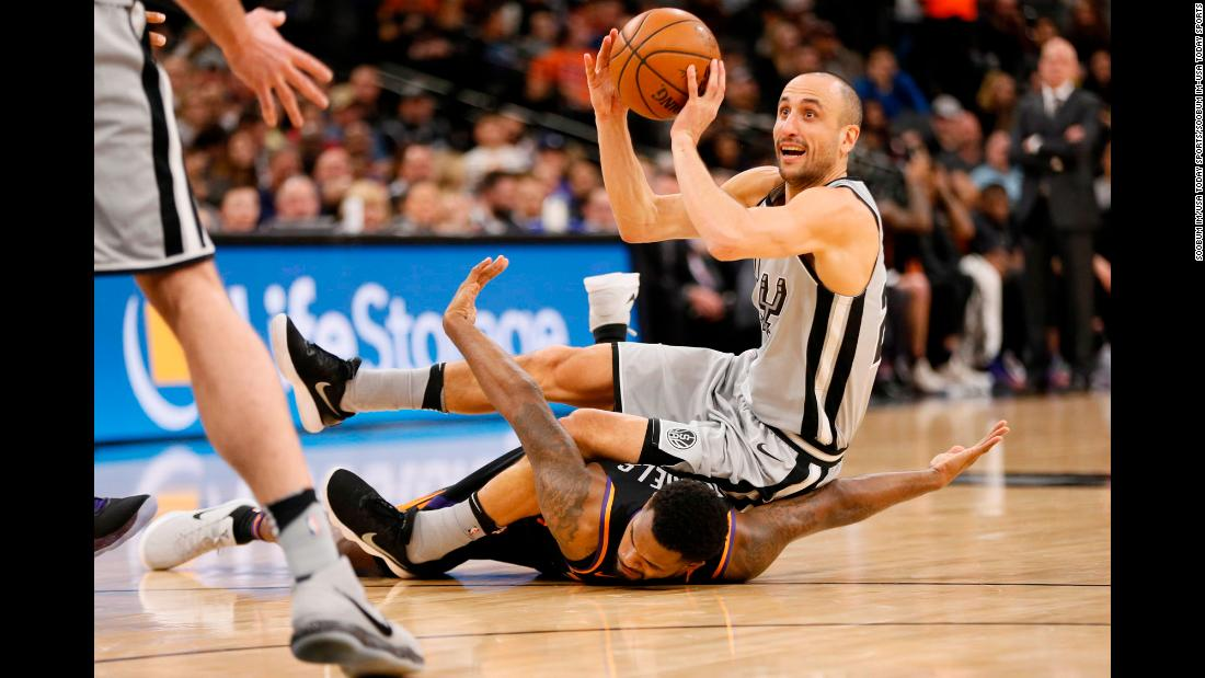 San Antonio guard Manu Ginobili looks to pass the ball as he falls over Phoenix's Troy Daniels during an NBA game on Friday, January 5.