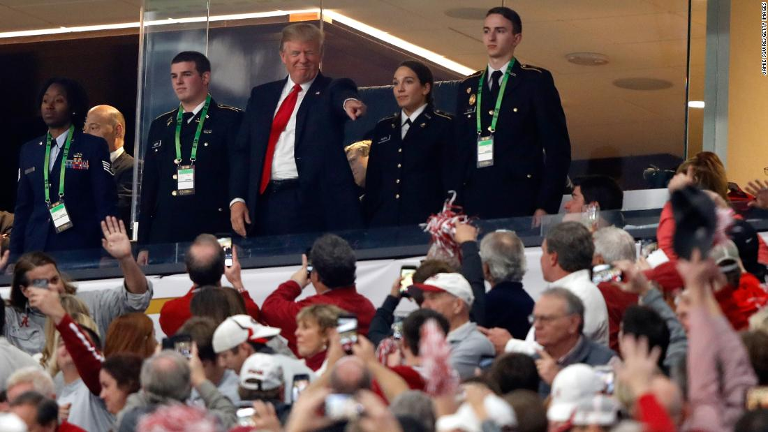 US President Donald Trump points to fans while attending the game.