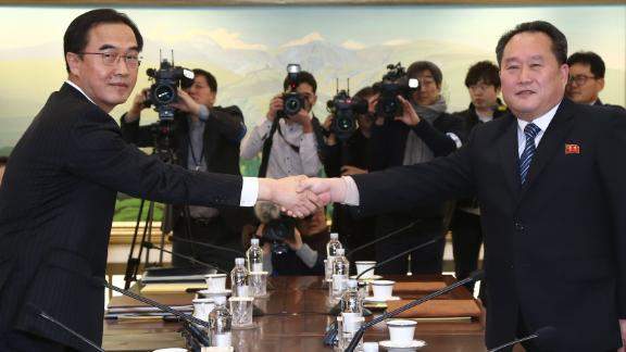 South Korean Unification Minister Cho Myoung-gyon (left) shakes hands with North Korea's chief delegate Ri Son-gwon prior to their meeting in the truce village of Panmunjom on January 9, 2018.