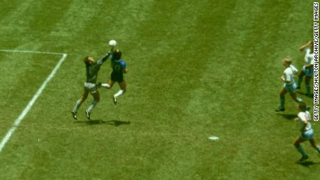 Diego Maradona outjumps England goalkeeper Peter Shilton to score his 'Hand of God' goal.